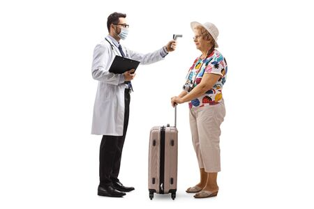 Full length profile shot of a male doctor measuring temperature to an elderly female tourist with a suitcase isolated on white background Zdjęcie Seryjne