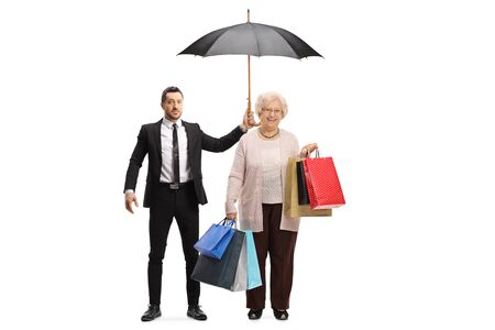 Full length portrait of a young man in a suit holding an umbrella over an elderly woman with shopping bags isolated on white background