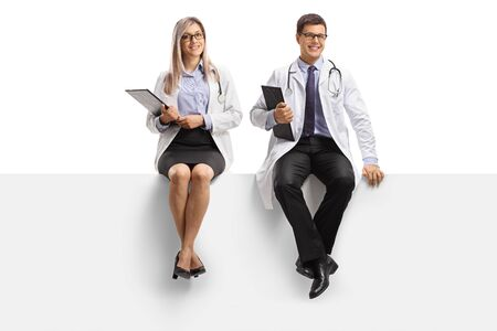 Full length portrait of a male and female doctors smiling and sitting on a blank panel isolated on white background