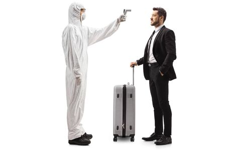 Full length profile shot of a man wearing a white protective suit and measuring temperature of a businessman isolated on white background