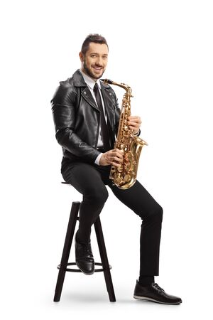 Man in a leather jacket sitting on a chair and holding a saxophone isolated on white background Stock Photo