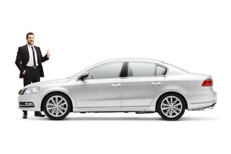 Businessman standing next to a silver car and showing thumbs up isolated on white background Foto de archivo