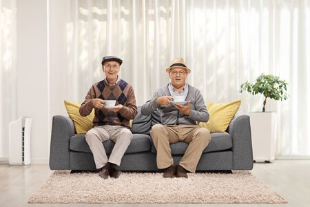 Two elderly men sitting on a sofa at home and drinking tea