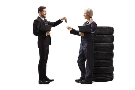 Full length profile shot of a businessman handing car keys to a female auto mechanic isolated on white background