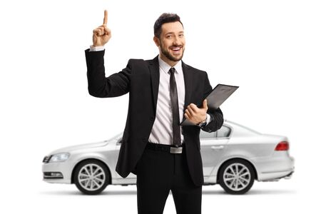 Car salesman standing in front of a silver car and pointing up isolated on white background