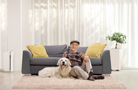 Mature man and a retriever dog sitting on the floor in a living room Stock fotó