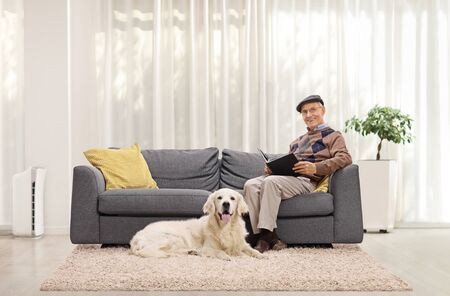 Elderly man at home reading a book on a sofa and his pet dog sitting beside him Stock fotó - 149389627