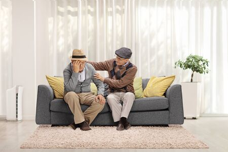 Elderly man comforting his sad friend and sitting on a sofa