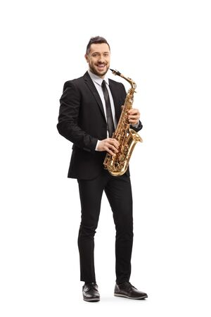 Full length portrait of a man in a suit standing and holding a saxophone isolated on white background