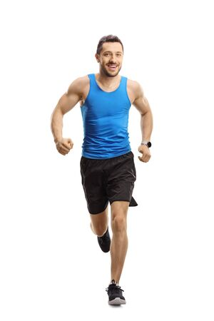 Full length portrait of a man in sportswear running towards the camera and smiling isolated on white background Archivio Fotografico