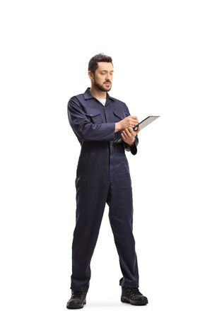 Full length portrait of an auto mechanic in a uniform standing and writing a document isolated on white background