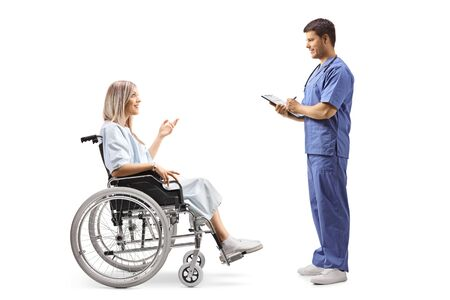 Full length profile shot of a young female patient in a wheelchair talking to a doctor isolated on white backgraund