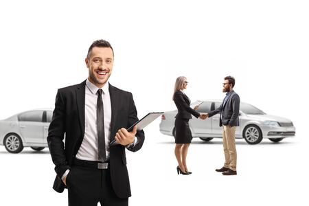 Car salesman posing in a showroom and a female shaking hands with a customer isolated on white background