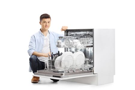 Casual young man next to an open dishwasher isolated on white background Banque d'images - 150370525