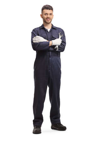 Auto mechanic holding a wrench and posing isolated on white background