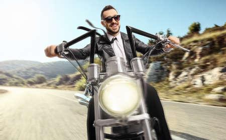 Biker with sunglasses riding a custom chopper on an open road