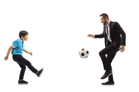 Full length profile shot of a father and son playing football isolated on white background
