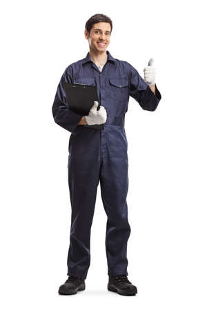 Full length portrait of a male worker in a uniform holding a clipboard and showing thumbs up isolated on white background