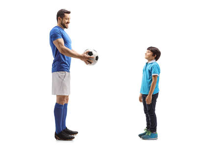 Full length portrait of an adult soccer player and a kid holding a ball isolated on white background