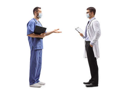 Full length profile shot of two medical workers with a protective masks talking isolated on white background Imagens