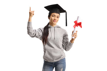 Happy female graduate student with a hat holding a diploma and pointing up isolated on white background