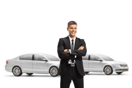 Professional man in a suit posing with crossed arms in a car showroom isolated on white background 免版税图像