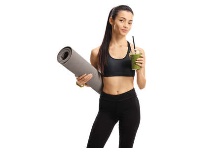 Young female in sportswear holding an exercise mat and a green smoothie isolated on white background Imagens