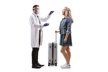 Full length profile shot of a doctor with face shield taking a cotton swab test from a female tourist isolated on white background Imagens