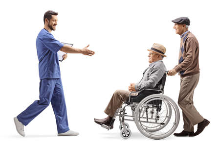 Full length profile shot of a male health worker walking and greeting and elderly patient in a wheelchair isolated on white background