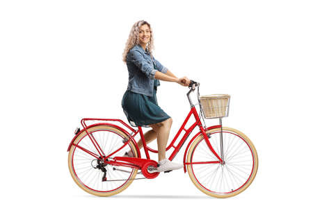 Side shot of a young woman in a dress riding a red bicycle and looking at the camera isolated on white background Imagens