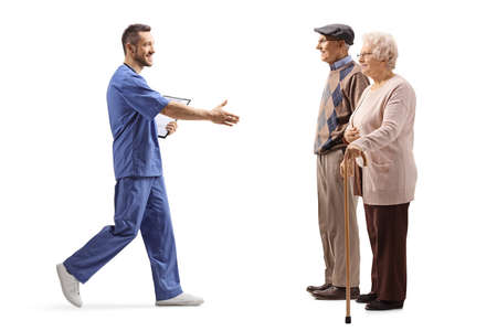 Full length profile shot of a male health worker walking and greeting elderly patients with hand isolated on white background