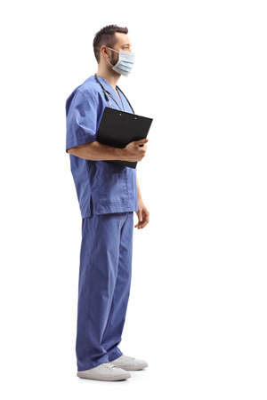 Full length profile shot of a medical worker in a blue uniform with a face mask isolated on white background