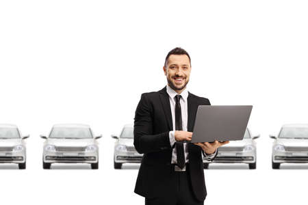 Car salesman working on a laptop computer and smiling at the camera in front of silver cars isolated on white background