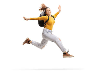 Female student with a backpack jumping high isolated on white background