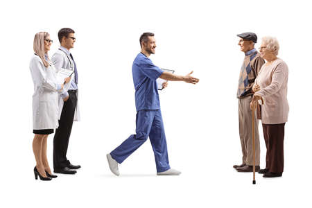 Doctors and a male nurse greeting elderly patients isolated on white background Imagens