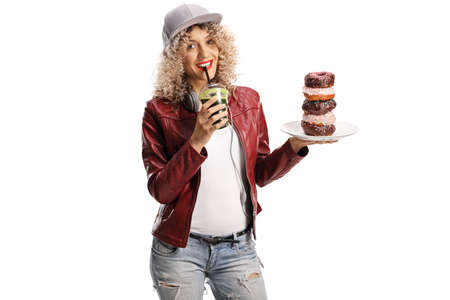 Trendy young woman holding a plate of chocolate donuts and drinking a green smoothie isolated on white background