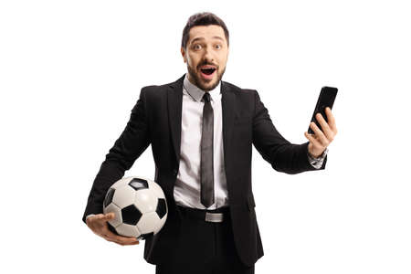 Excited man in a suit holding a soccer ball and a mobile phone isolated on white background