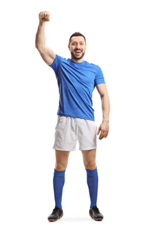 Full length portrait of a soccer player in a blue top and white shorts raising a hand isolated on white background