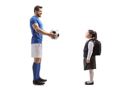 Full length profile shot of a footballer giving a soccer ball to a schoolgirl isolated on white background