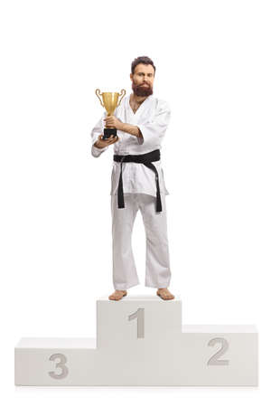 Full length portrait of a karate champion in kimono with a trophy cup on a winners podium isolated on white background