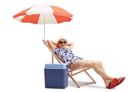 Elderly man enjoying  a holiday on a deckchair under umbrella isolated on white background