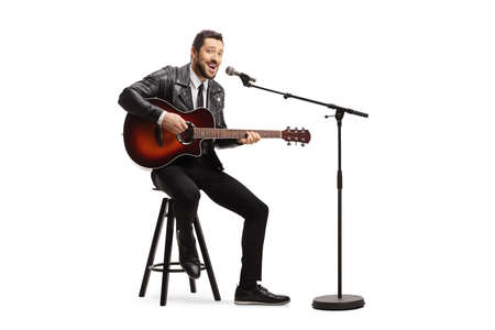 Man playing an acoustic guitar and singing on a microphone isolated on white background