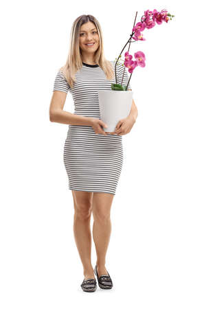 Full length portrait of a woman holding a pink orchid in a pot isolated on white background Imagens
