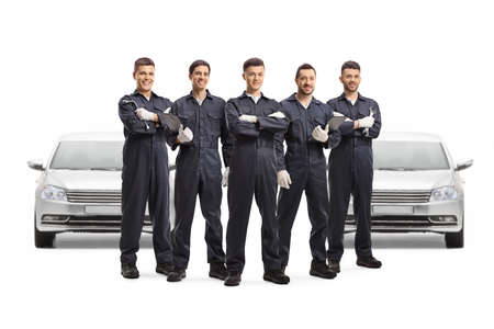 Group of auto mechanic workers posing in front of two cars isolated on white background