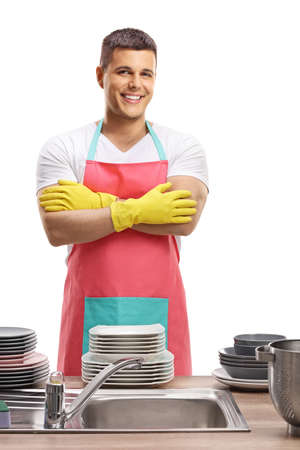 Handsome young man with apron standing behind a sing with clean dishes isolated on white background
