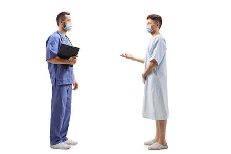 Full length profile shot of a medical worker in a blue uniform with a face mask and a patient talking isolated on white background Imagens