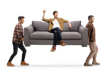 Two young men carrying a sofa with a man sitting on it and pointing up isolated on white background Imagens