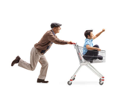 Full length profile shot of an elderly man running and pushing a shopping cart with a boy inside isolated on white background