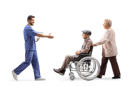 Full length profile shot of a male health worker walking and welcoming elderly man in a wheelchair isolated on white background 版權商用圖片
