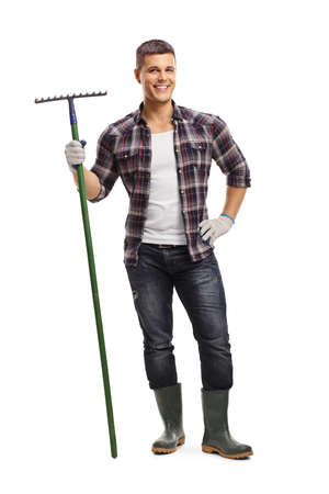 Full length portrait of a cheerful young farmer holding a rake isolated on white background Zdjęcie Seryjne
